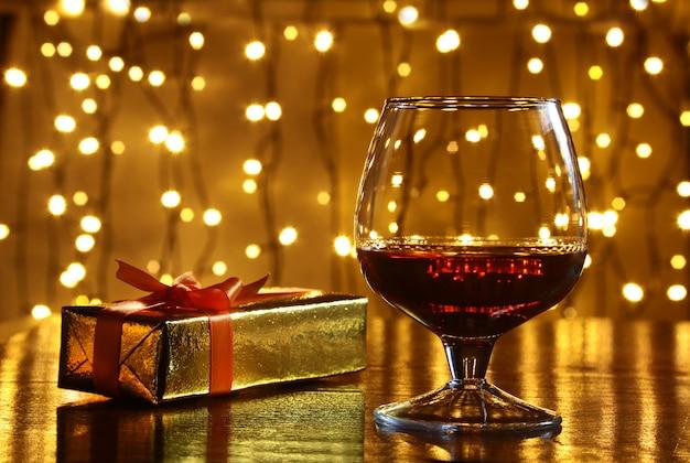 Whisky, cognac, brandy e confezione regalo sul tavolo di legno. celebrazione composizione sulla luce