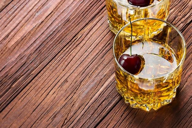 Whisky con ghiaccio e ciliegia in due bicchieri