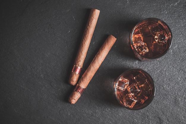 Whisky con ghiaccio e sigaro. copia spazio
