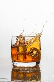 Whisky con ghiaccio in un bicchiere con spruzzi