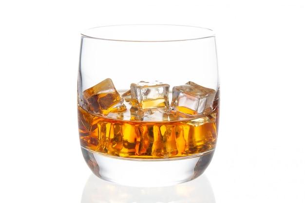 Whisky con ghiaccio in vetro isolato su uno sfondo bianco