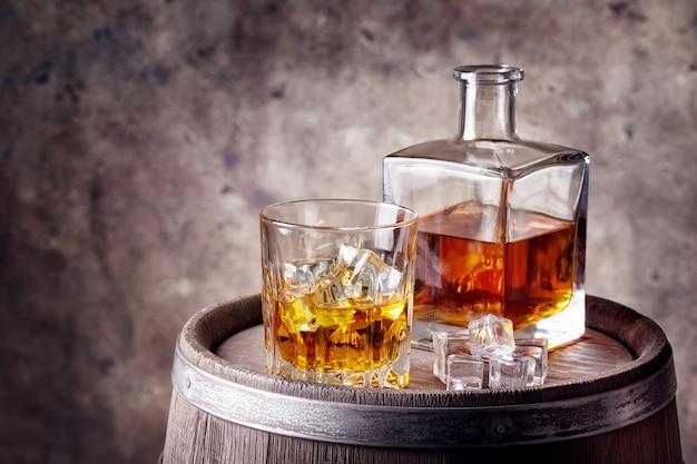 Whisky con ghiaccio su botte di legno
