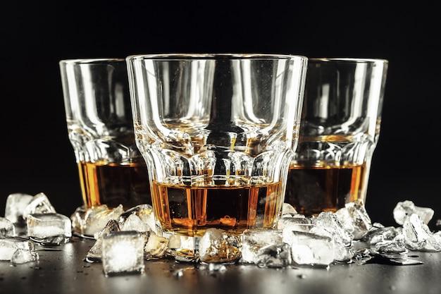 Whisky e ghiaccio su legno rustico