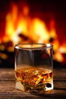 Whisky in un bicchiere con camino sfocato