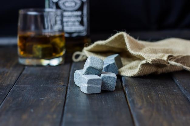 Whisky in un bicchiere con pietre per il raffreddamento di bevande su un tavolo di legno
