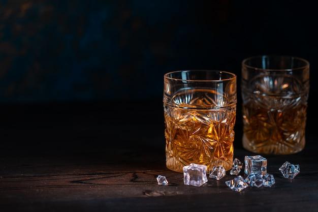 Whisky in vetro con sfondo di ghiaccio
