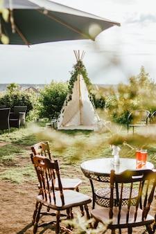 Wigwam in tessuto di legno decorato con rami di eucalipto verde nel cortile, evento o matrimonio in stile boho
