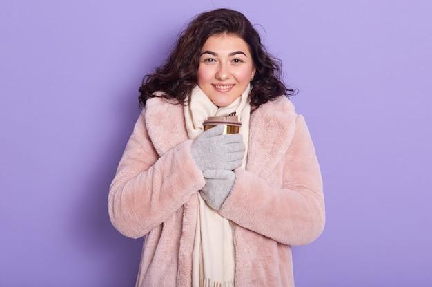 Wimsome congelamento giovane donna che beve bevanda calda, cercando di crogiolarsi le mani