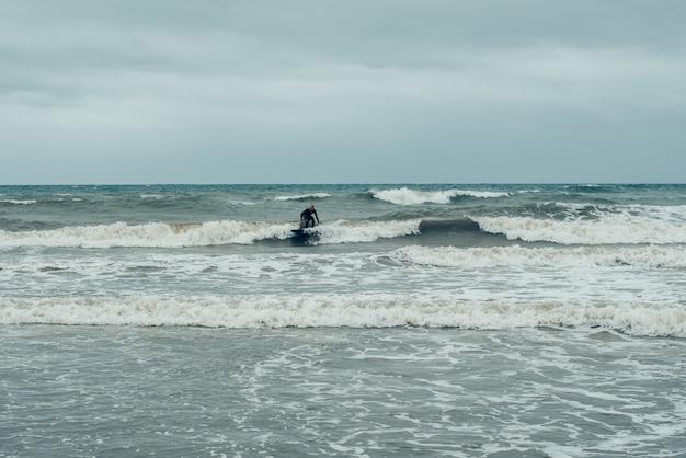 Windsurfer che provano a cavalcare le piccole onde durante la tempesta.