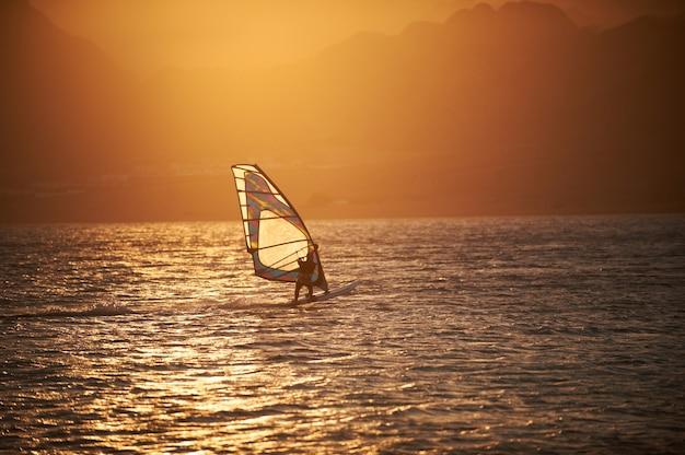 Windsurfista di sportman sulla superficie del mare contro le montagne a tempo di tramonto
