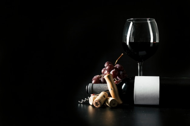 Wineglass e bottiglia vicino cavatappi e uva