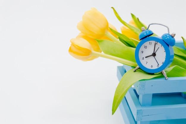 Womans holiday yellow primavera tulipani con una sveglia e carrello di legno blu