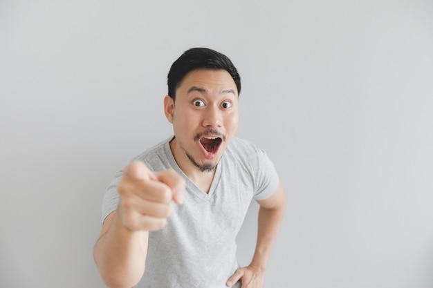 Wow e faccia sorpresa dell'uomo in maglietta grigia con punto della mano su spazio vuoto.