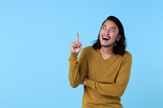 Wow e giovane uomo asiatico sorpreso che sorride con il suo dito che indica sullo spazio blu con lo spazio della copia.