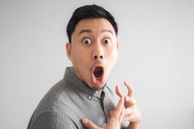 Wow e volto sorpreso di bell'uomo divertente con segno mano indicando.