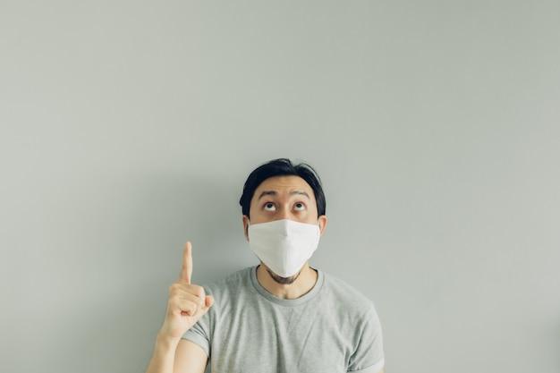 Wow faccia di uomo che indossa una maschera igienica e una maglietta grigia.