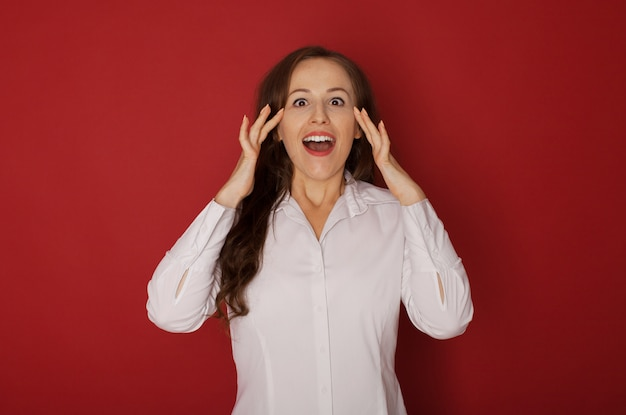Wow. mezzo busto ritratto femminile isolato su sfondo rosso studio. giovane donna sorpresa emozionale che sta con la bocca aperta. emozioni umane, concetto di espressione facciale.