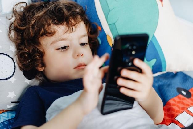 Wow, mi piace quel telefono. bambino con smartphone. ragazzo che si siede nel letto e che gioca con il telefono cellulare. chiamando mia mamma. carino piccolo bambino tiene il cellulare in mano e guardando attentamente lo schermo.