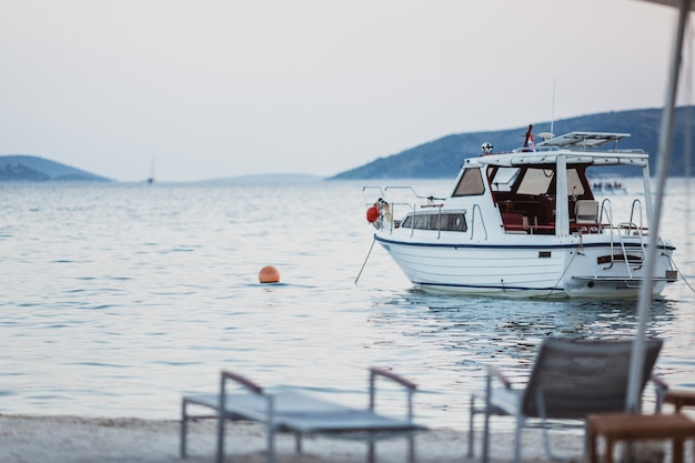 Yacht bianco con bandiera croata nel bellissimo mare blu turchese in piedi vicino alla spiaggia