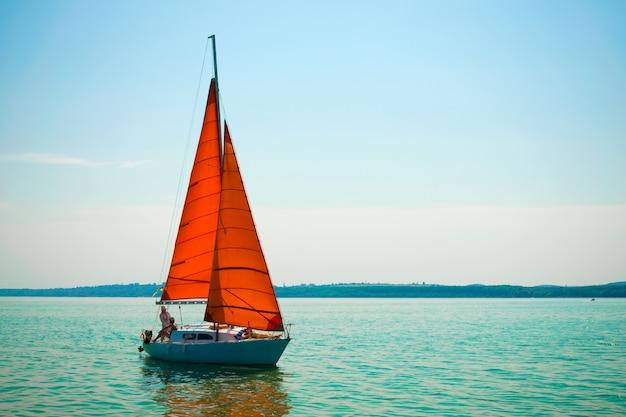 Yacht con vele rosse scarlatte sul lago