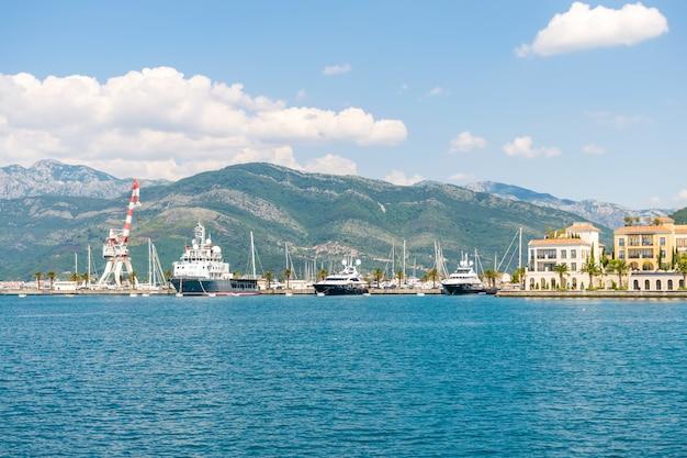 Yacht di varie dimensioni e grandi navi ormeggiate nel porto di teodo