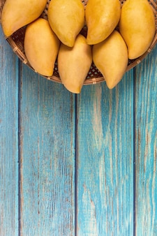Yellow fresh mangos 0n tavolo in legno blu. mango frutta tropicale. mango. concetto di estate.