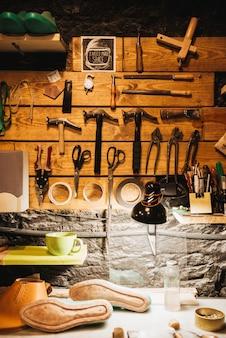 Ynstruments sulla parete di legno all'officina delle calzature.