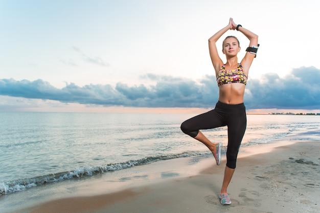 Yoga adatta di pratica della ragazza dei giovani sulla spiaggia all'alba