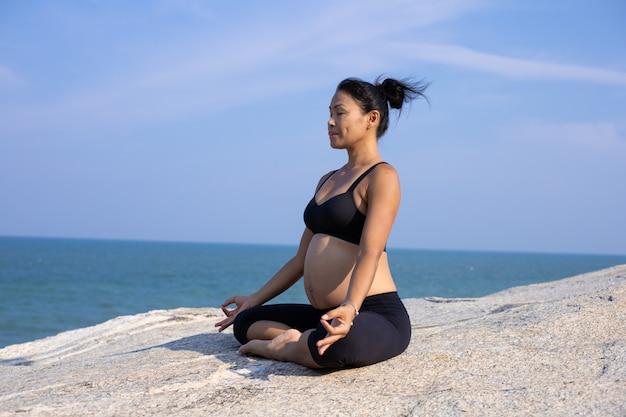 Yoga asiatica della donna incinta sull'ora legale di tramonto della spiaggia