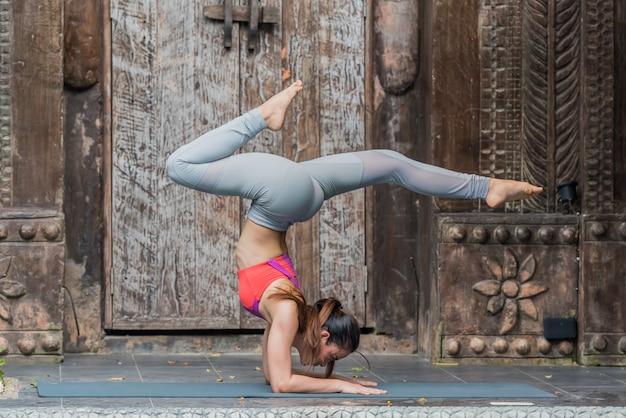 Yoga asiatica di pratica della donna asiatica e allungare esercizio di allenamento nella classe di yoga