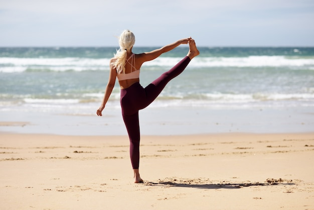 Yoga bionda caucasica di pratica della donna nella spiaggia