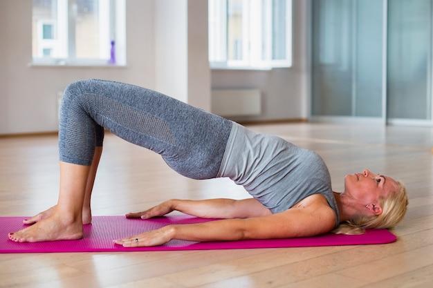 Yoga di pratica adatta della donna bionda