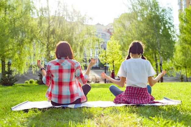 Yoga di pratica dell'adolescente della figlia e della mamma in parco