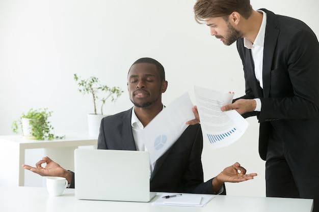 Yoga di pratica dell'uomo d'affari afroamericano calmo sul lavoro che trascura capo arrabbiato