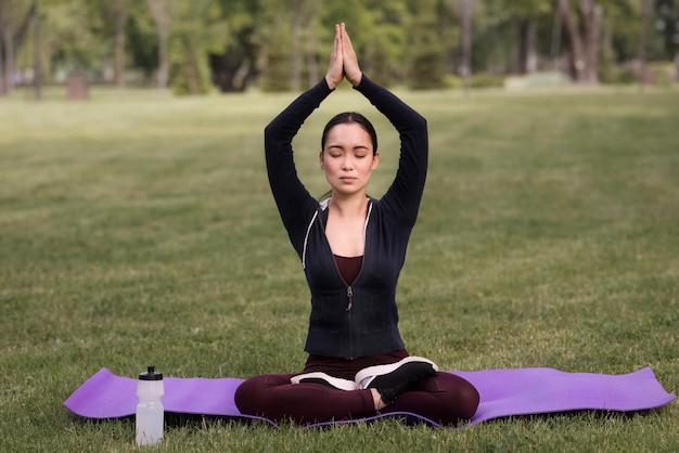 Yoga di pratica della bella donna all'aperto