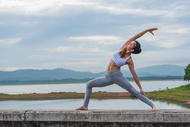 Yoga di pratica della bella donna dal lago con la montagna.