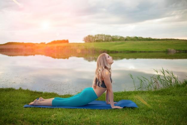 Yoga di pratica della bella ragazza bionda atletica sul lago al tramonto, primo piano, sostiene uno stile di vita sano
