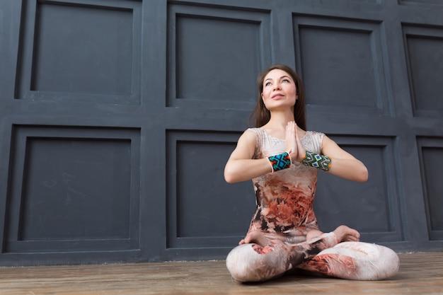 Yoga di pratica della donna attraente, mentre sedendosi nella posa del loto