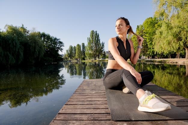 Yoga di pratica della donna attraente su una stuoia su un pilastro vicino al lago di mattina