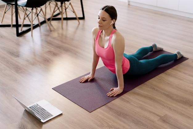Yoga di pratica della donna caucasica a casa