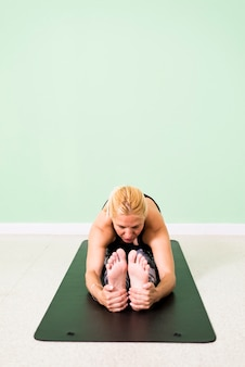 Yoga di pratica della donna che si siede nella posizione di paschimottanasana (curvatura di andata messa) sul pavimento