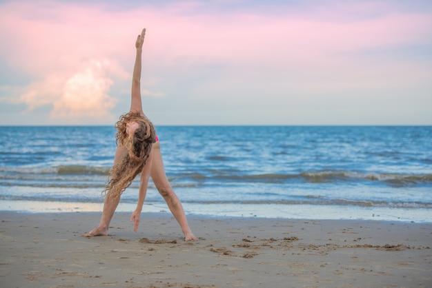 Yoga di pratica della donna dei capelli biondi sulla spiaggia.