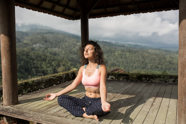 Yoga di pratica della donna nel gazebo tradizionale di balinesse.