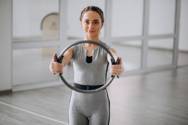 Yoga di pratica della donna nella palestra su una stuoia