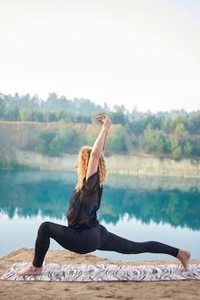 Yoga di pratica della donna riccia attraente o del modello della testarossa all'aperto