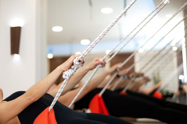 Yoga di pratica della donna sulle corde che allungano in palestra.
