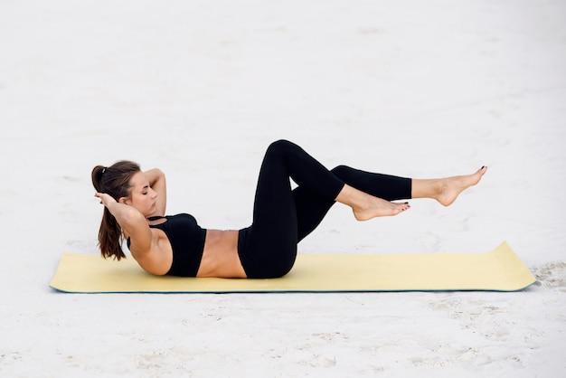 Yoga di pratica della giovane bella donna, facendo esercizio di press up sulla spiaggia del mare. yoga fitness e concetto di stile di vita sano. la bella donna negli sport indossa fare l'esercizio sulla stuoia di yoga.