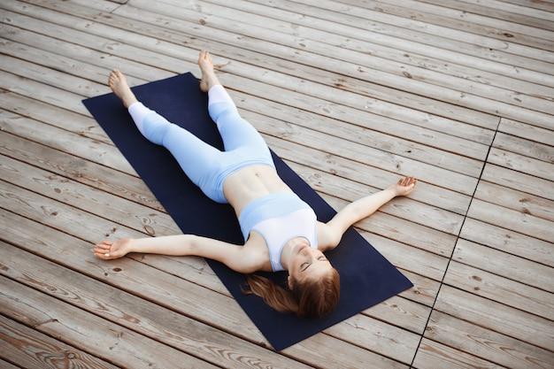 Yoga di pratica della giovane bella ragazza bionda fuori.