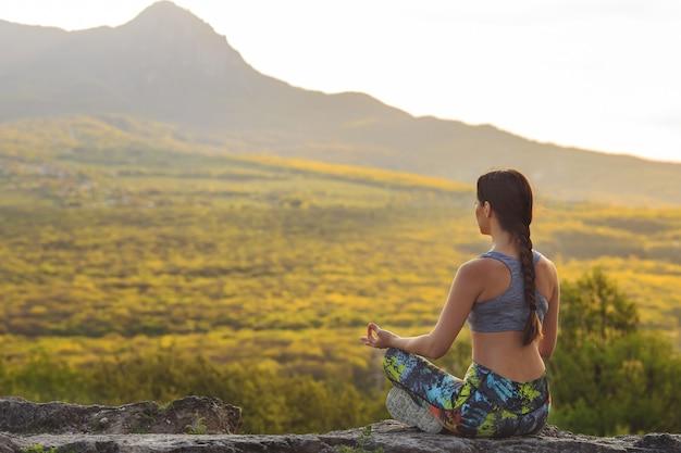 Yoga di pratica della giovane donna al tramonto nella bella posizione della montagna.