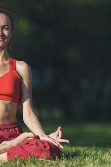 Yoga di pratica della giovane donna all'aperto. la femmina medita all'aperto nel parco della città dell'estate.
